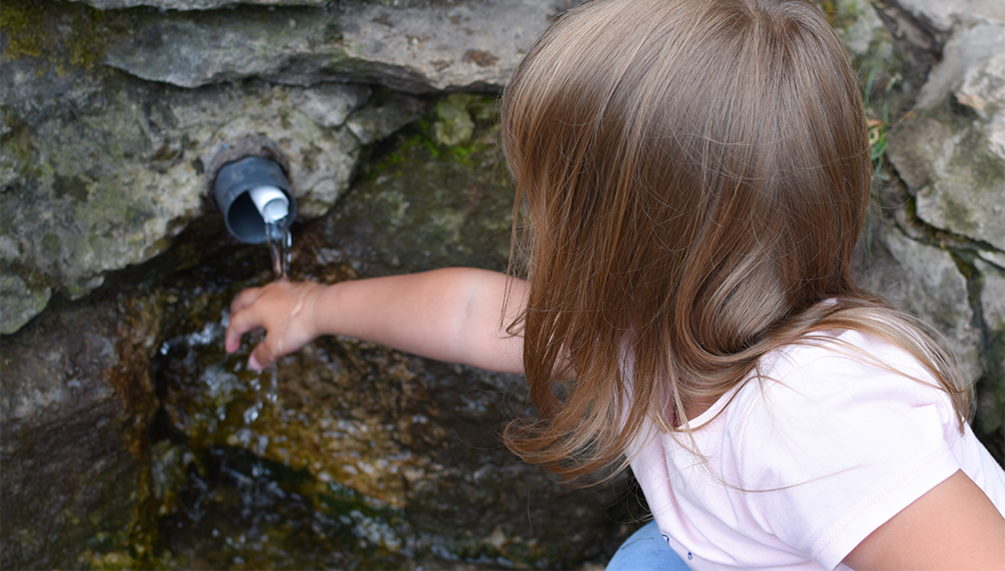 Little girl touching spring water
